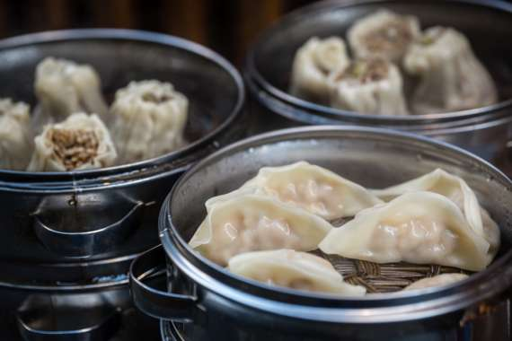 Delicious traditional chinese dumplings steamed and filled with pork meat, prepared on hot steam, China